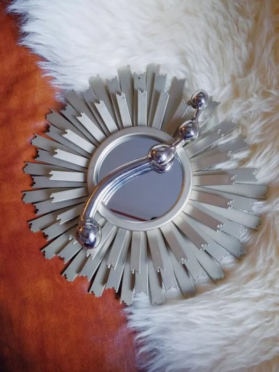 [Image: njoy fun wand stainless steel beaded s-curved dildo on mirror on leather and white fur]