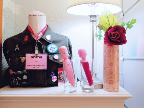 [Image: Pink BMS Factory Pillow Talk Cheeky and Blush Noje W4 Wand vibrators on display in cups in front of a mannequin with jacket and enamel pins]