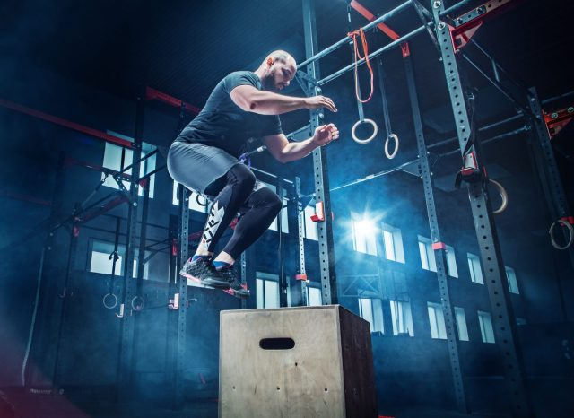 Man jumping during exercises in the fitness gym. CrossFit concept. gym, sport, rope, training, athlete, workout exercises concept