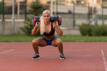 Sandbag squats. Functional fitness. Leg strengthening exercises.