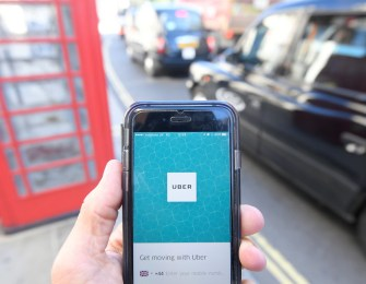 A photo illustration shows a London taxi passing as the Uber app logo is displayed on a mobile telephone, as it is held up for a posed photograph in central London