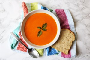 Easy Roasted Tomato Soup made at home, a wonderful orange colour garnished with bright green basil and sserved with a hunk of white bread. Recipe at Supper in the Suburbs