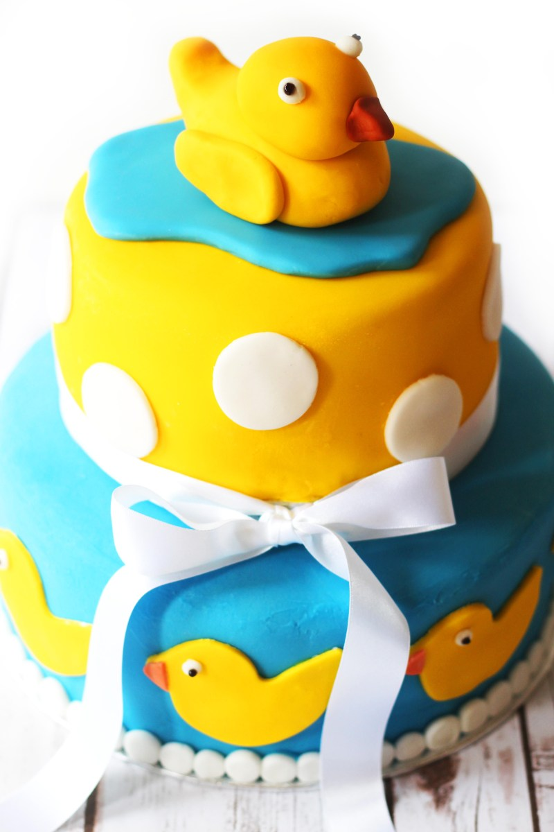 Two tier celebration cake, perfect for a baby shower complete with rubber duckies and polka dots!