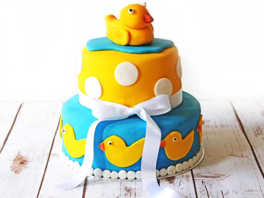 This Two tier celebration cake, perfect for a baby shower complete with rubber duckies and polka dots!