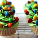 Christmas Tree Cupcakes iced with bright green buttercream swirl and M&M fairy lights