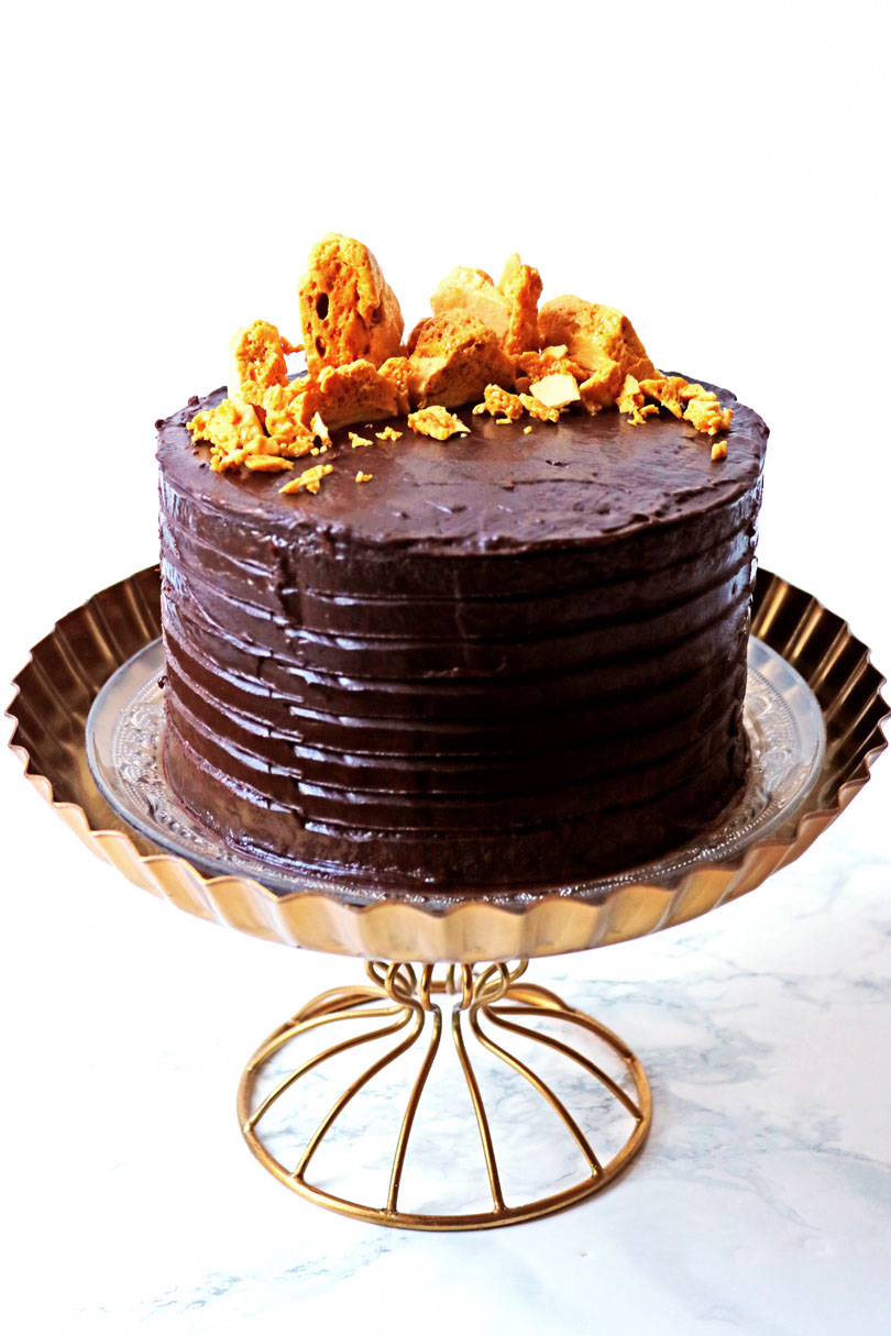 This Cinder Toffee Bonfire Cake is smothered in milk and dark chocolate ganache and topped with honey comb. It's the perfect cake to serve up this bonfire night.