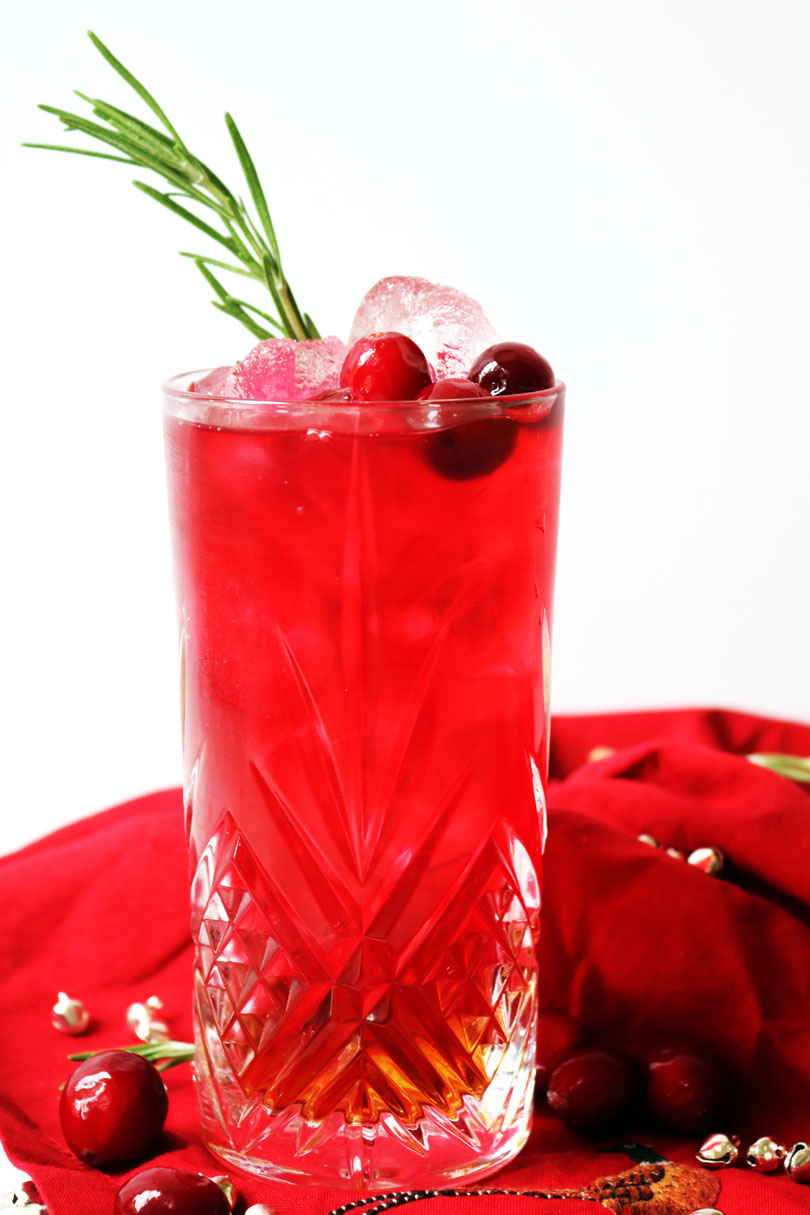 A long, tall glaas of cranberry juice and amaretto served over ice and garnished with fresh cranberries and rosemary