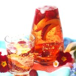 Carafe of rose sangria, poured over raspberries and nectarine wedges