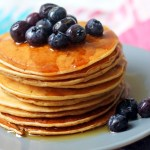 A large stack of vegan American style pancakes with maple syrup and blueberries