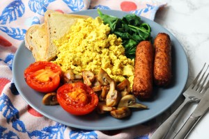 A plate of toast, grilled tomatoes, sauteed mushrooms, spinach, vegetarian sausages and tofu scramble