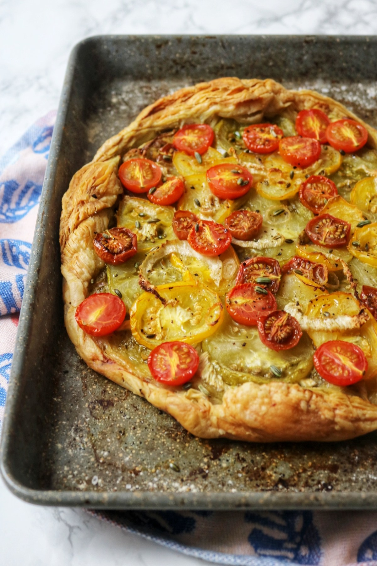 Up close shot of a tomato and fennel tart on a baking sheet