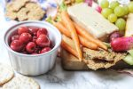 Vegan cheese served with pickled cherries, grapes, crackers and carrots