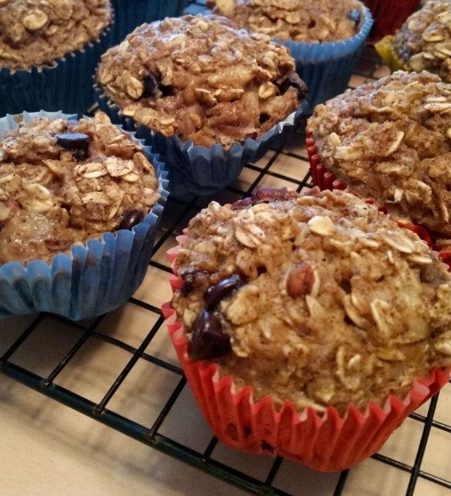 A close up of Banana Oatmeal Chocolate Chip Muffins in blue and red liners cooling on a cookie rack