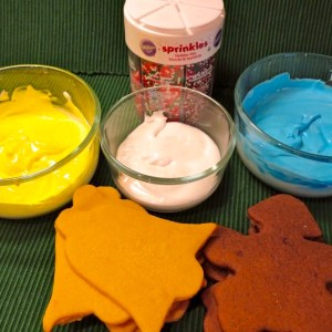 Decorating cookies with Royal Icing. Three colors of icing, sprinkles and cut out cookies ready to decorate.
