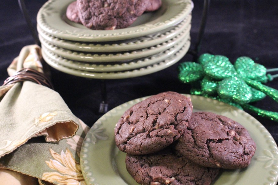 Chewy Chocolate Mint Cookies stacked on a green plate with a shamrock next to it