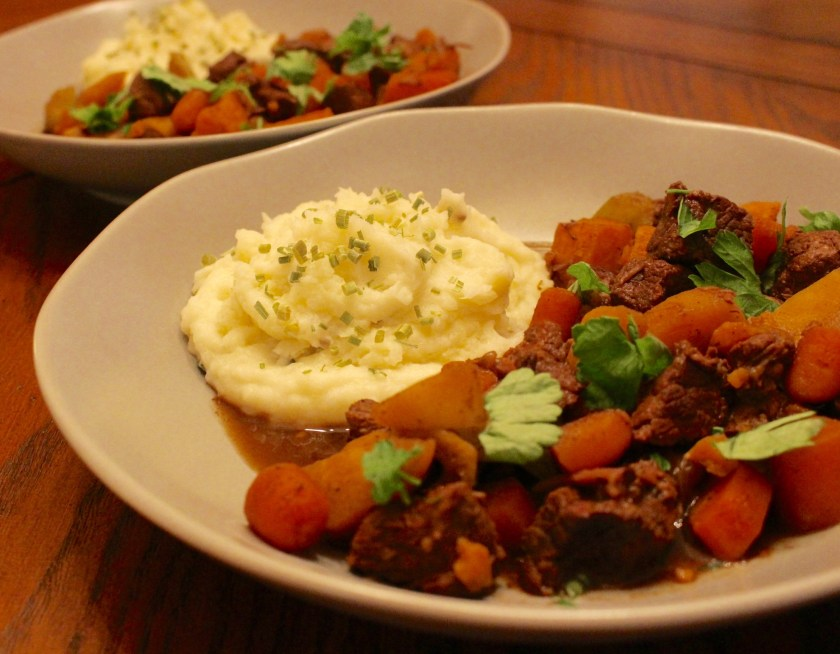 Beef Stew with Parsnips served in a bowl with a side of mashed potatoes