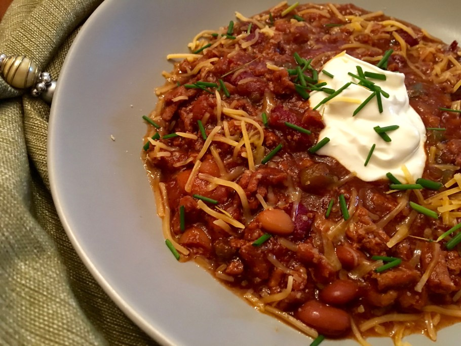 Guinness Chili in a green bowl Closeup with sour cream and chives