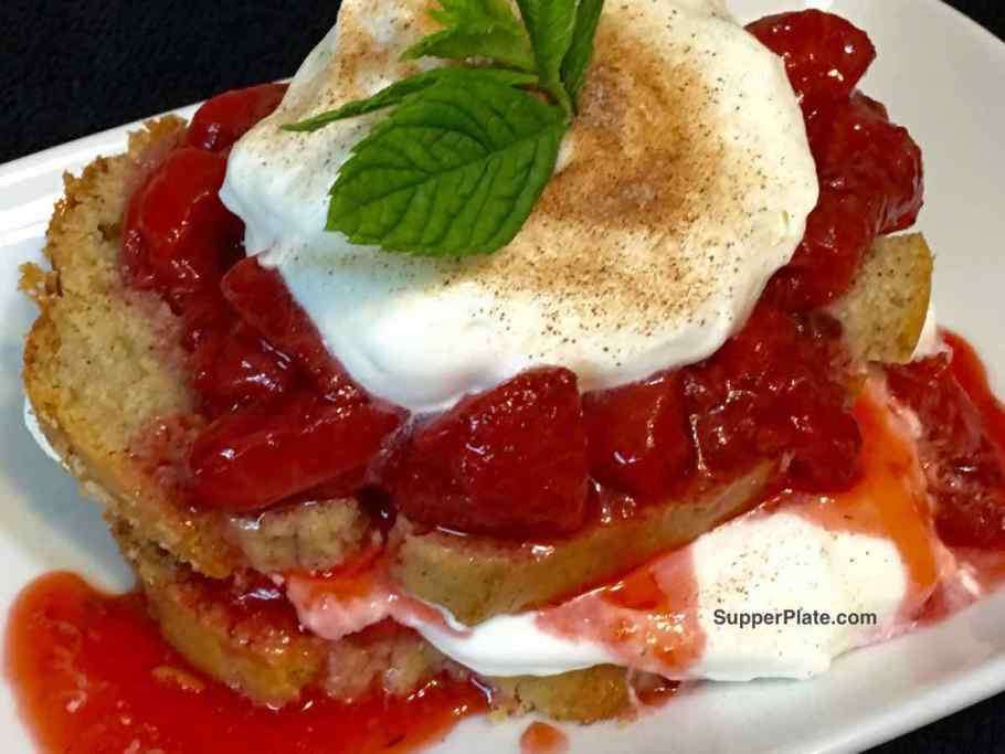 Strawberry Shortcake with Bourbon Sauce on a white plate topped with homemade whipped cream and mint leaves