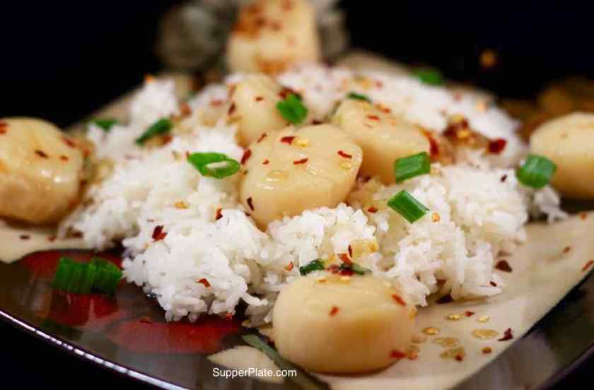 Caramelized Scallops plated on top of a bed of rice rice with crushed red pepper flakes and green onions