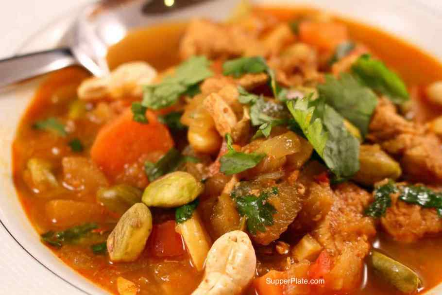 A bowl of Chicken Curry Soup topped with raw cashews and cilantro