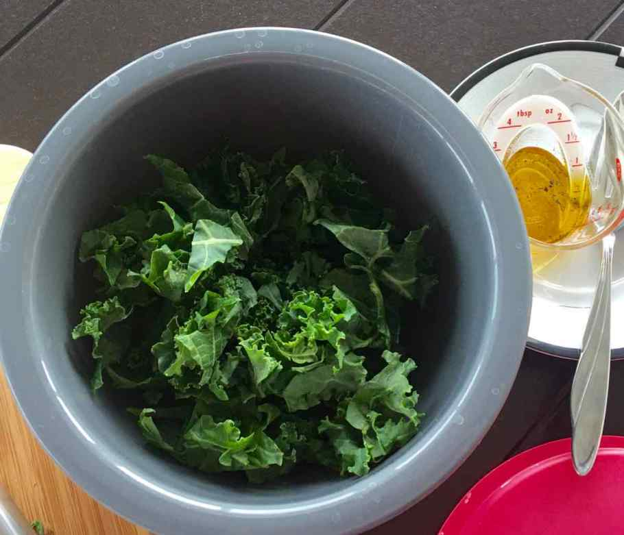 Adding some of the kale to the bowl before the dressing