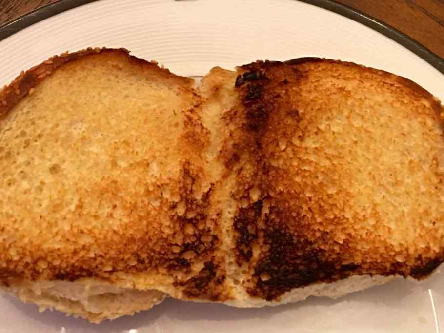 A toasted roll is on a white plate