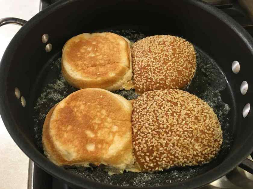 Toasting the seeded rolls in a black skillet