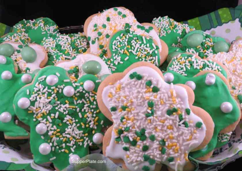 Many decorated shamrock cookies on a plate