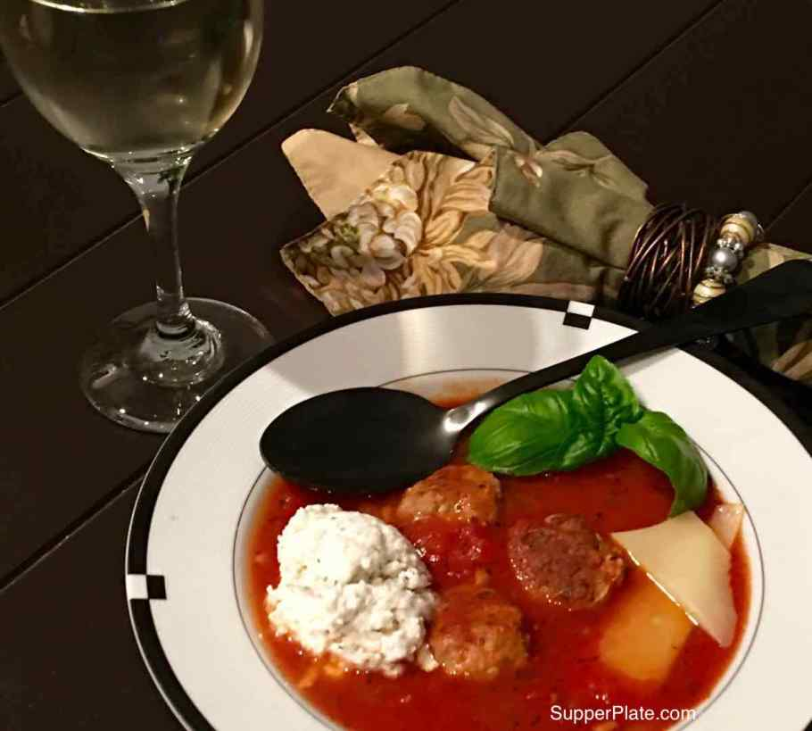 Top view of a bowl of lasagna soup in a white bowl with a green napkin and glass of wine