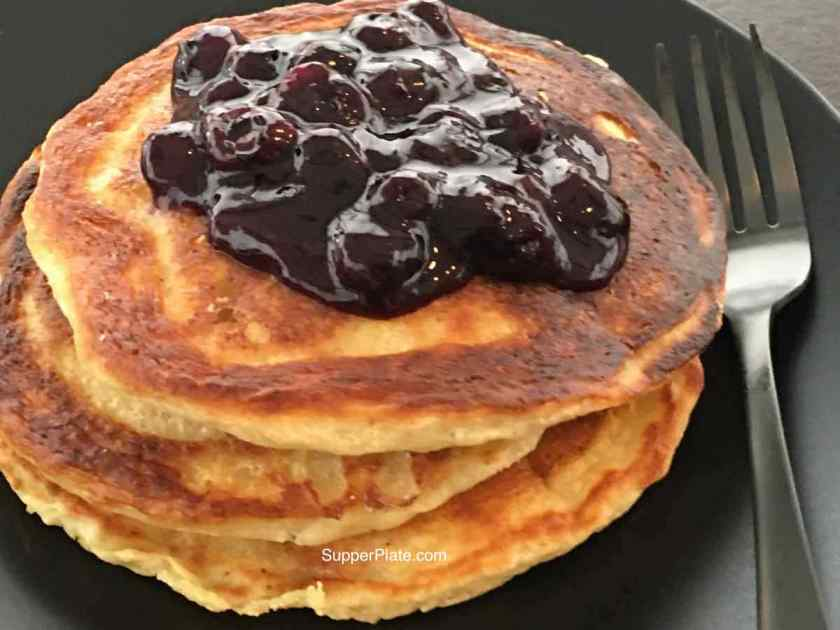 Stack of pancakes on a black plate with black fork topped with blueberry sauce
