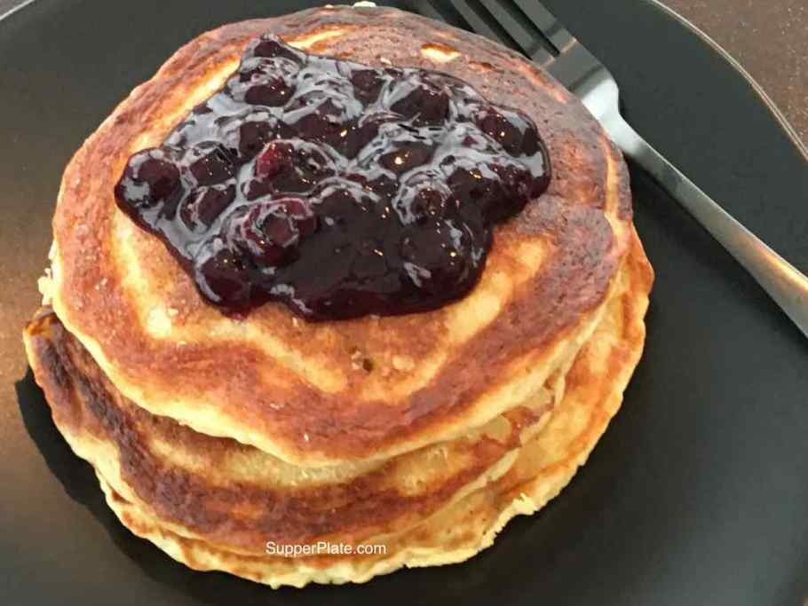 Top view of a stack of pancakes on a black plate with black fork topped with blueberry sauce
