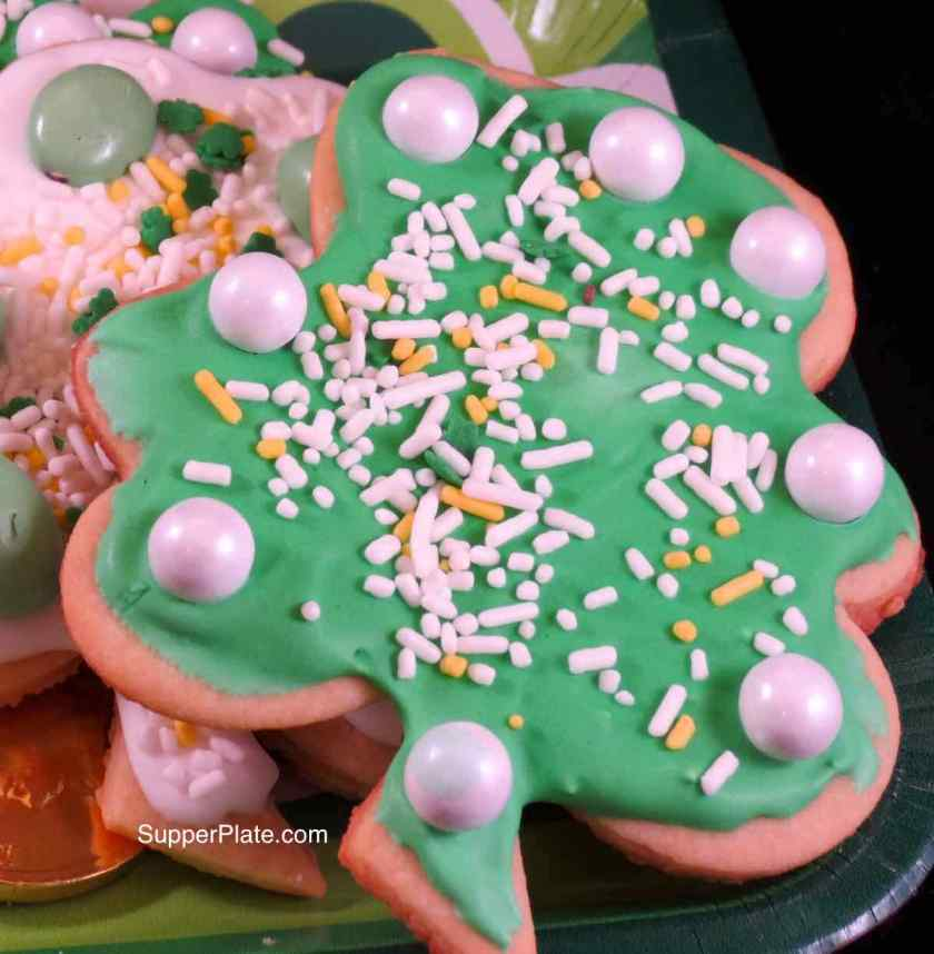 A cookie decorated with green icing and white pearls with sprinkles