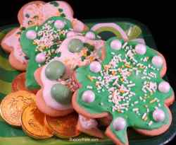 Shamrock cookies on a plate with gold coins