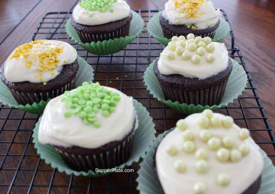 Side view of cupcakes in green liners decorated with frosting and toppings on a cooling rack