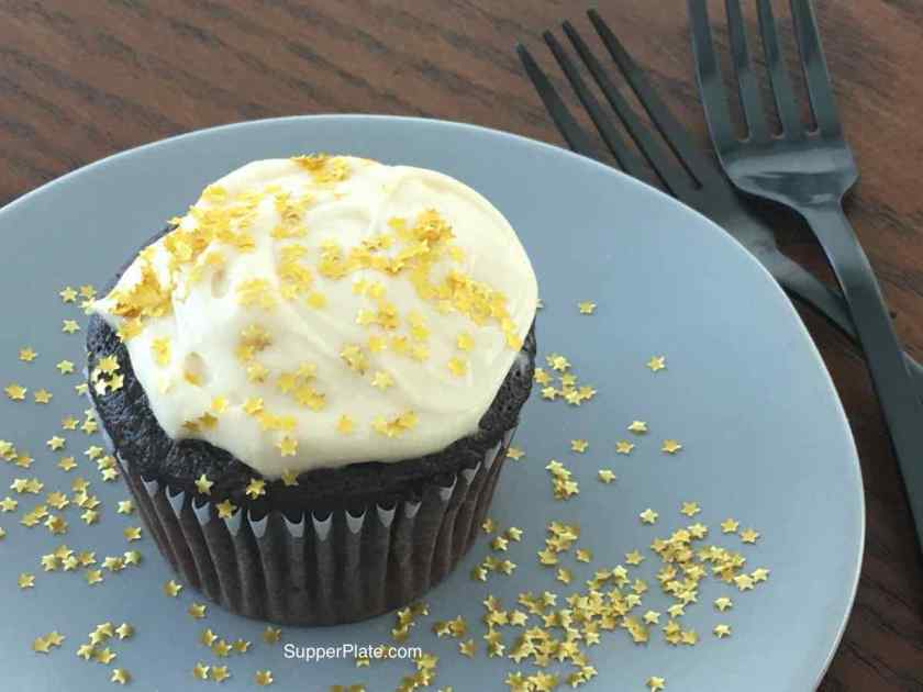 Cupcake with frosting on a green plate with gold stars with two black forks