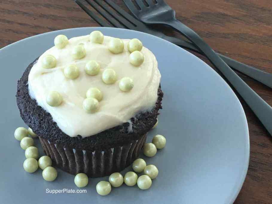 Decorated cupcake on a green plate with black forks