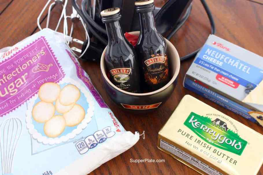 Closeup of Confectioners Sugar bag, Kerrygold butter, cream cheese, Baileys and hand mixer