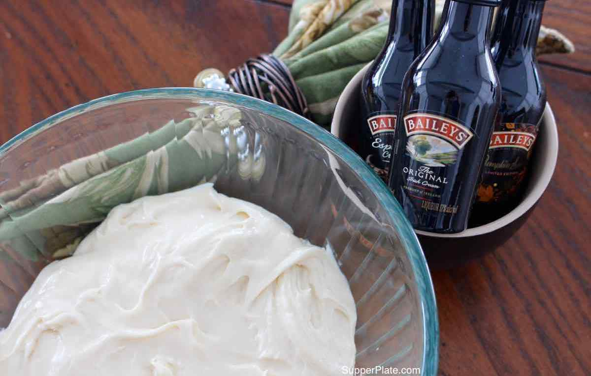 Side view of frosting in a clear bowl with a green napkin and Baileys Irish Cream Small Bottles