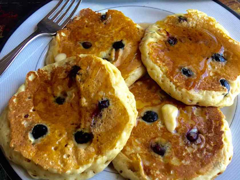 Four blueberry pancakes on a plate with butter and a fork