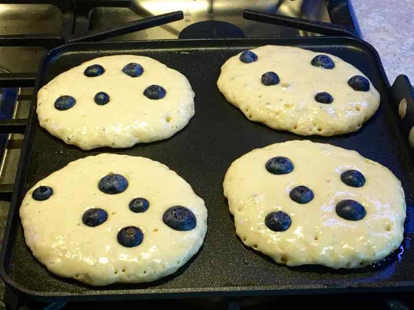 Pancakes on griddle with blueberries