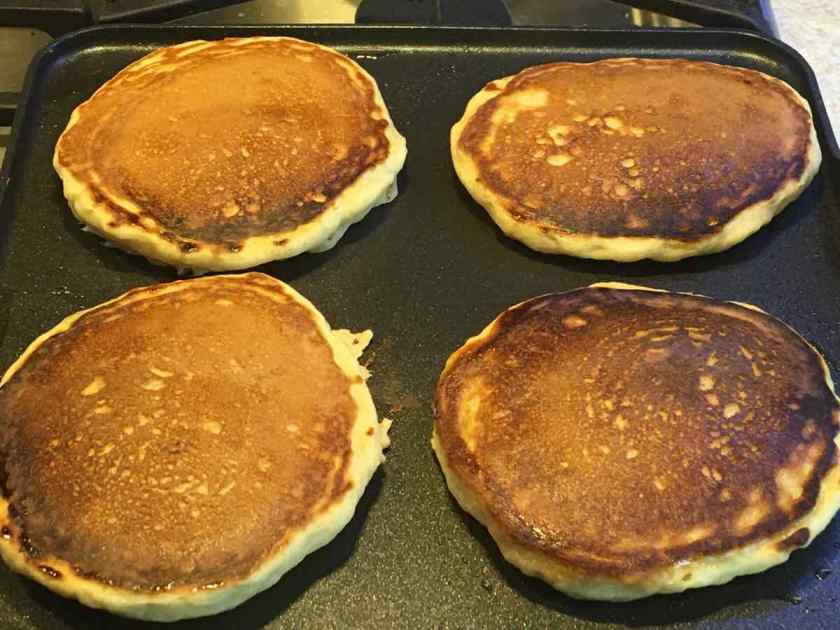 Four golden brown Pancakes on griddle