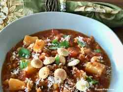 Side view of Beef Minestrone Soup in a green bowl with a green napking
