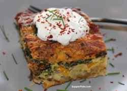 Breakfast Casserole with Bacon on a plate topped with sour cream chives with a black flork