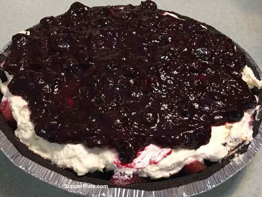 No Bake Mixed Berry Cheesecake topped with a blueberry sauce