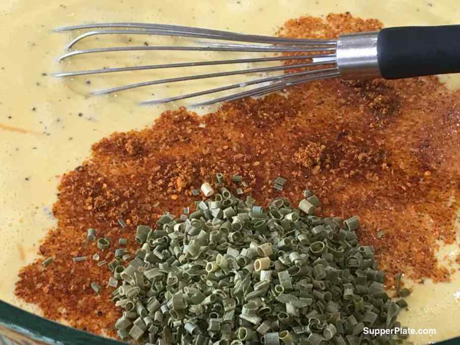 spices added to the egg mixture in a bowl with a whisk