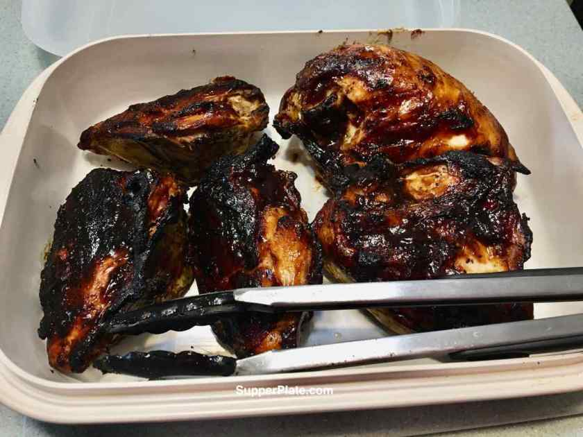 BBQ chicken on a platter with cooking tongs
