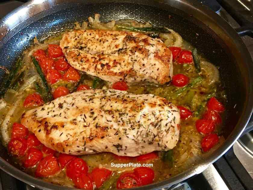 Seasoned chicken in a stainless steel nonstick pan