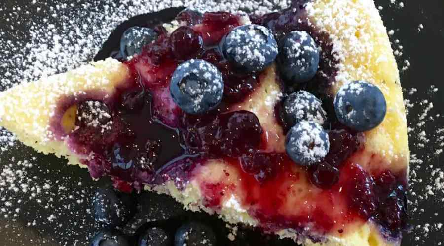 Top view of Lemon Blueberry Cake with Blueberry Glaze on a black plate topped with powdered sugar
