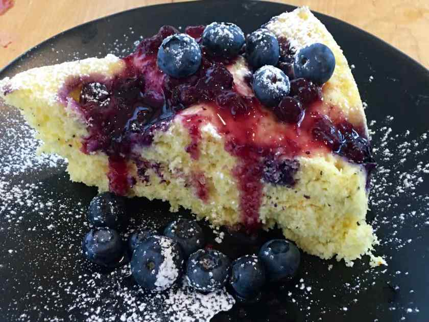Lemon Blueberry Cake on a black plate topped with blueberry sauce and blueberries