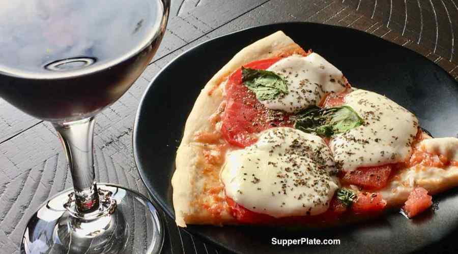 margarita pizza on a black plate with a glass of red wine
